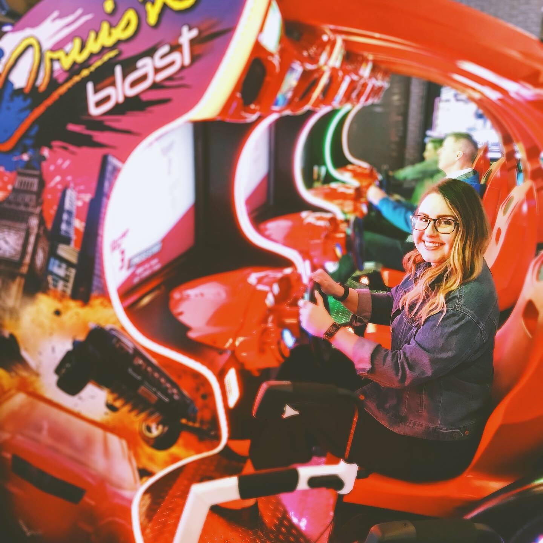Lisa sitting behind the steering wheel at a racing arcade game.
